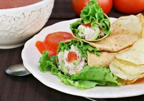 Healthy tuna salad wraps with a side of chips.  Bowl of tomato soup and fresh tomatoes in the background.