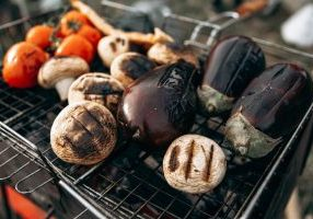Tomatoes, mushrooms and eggplant grilling on barbecue lattice